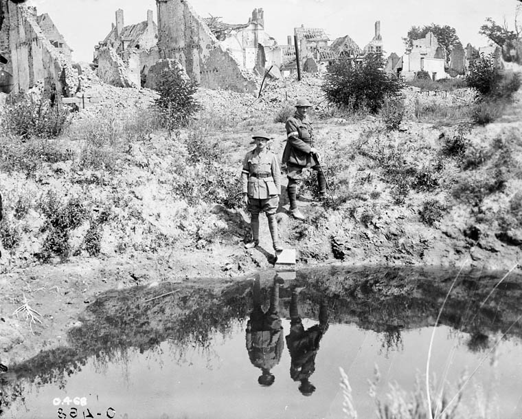 A 17' shell hole in the Main Square, Ypres. Brig.-Gen. Burstall and Captain Papineau. July, 1916. (item 1)