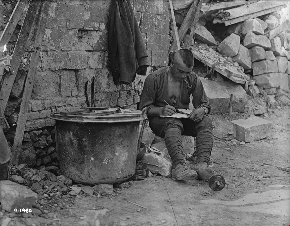 Soldier sitting writing a letter
