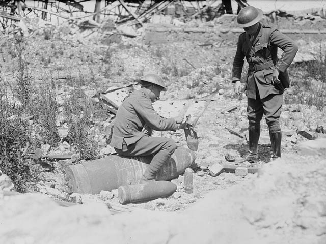 Unexploded shell being examined by Canadian troops. (item 1)