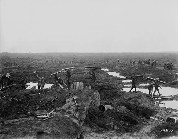 Canadian Pioneers carrying trench mats with wounded and prisoners in background during the Battle of Passchendaele. (item 1)
