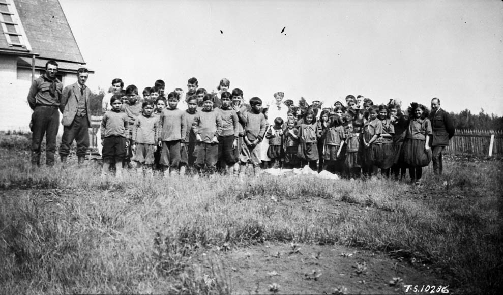 Hay River Indian Residential School (St. Peter's Mission), group of students and school officials posing beside a building, 1925