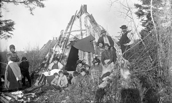 Group of Mi'kmaq men, women and children sitting and standing in front of a tent constructed from skins and birch logs, Elmsdale, Nova Scotia, 1891
