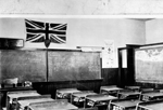 Black and white photograph of a classroom with a teacher's desk, rows of students' desks, and blackboards at the front and side.  A large Union Jack is suspended over the blackboard at the front of the class.