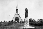 Black and white photograph of a statue in front of a church