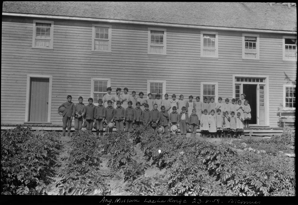 All Saints Indian Residential School, students outside the school by a garden, Lac La Ronge, unknown date
