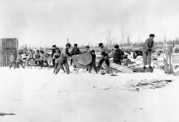 Fort Resolution Indian Residential School (St. Joseph's Convent), students cutting firewood in the snow, date unknown