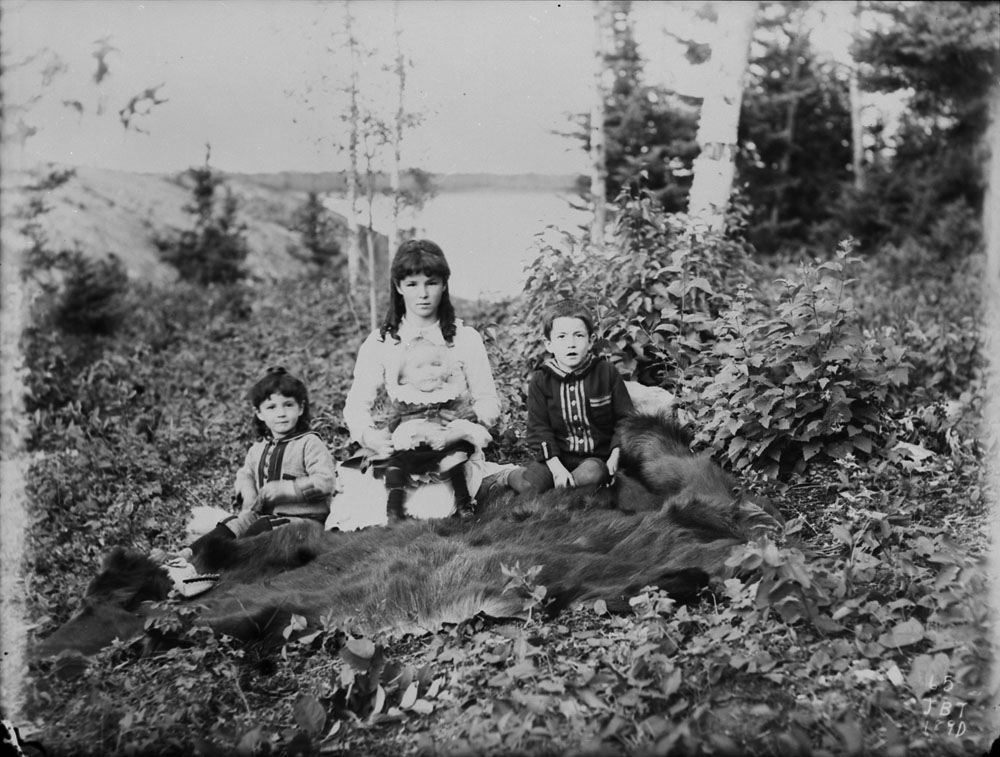 Four Métis children seated on a bear skin on the ground in the woods, Berens River, Manitoba, 1890