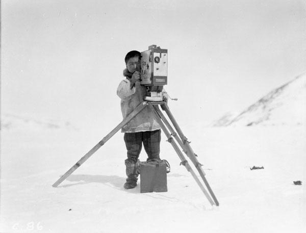 [Unidentified Inuk man looking through the lens of a movie camera on a tripod, Kangiqsujuaq, Nunavik] Original title: Eskimo with Mr. George Valiquette's movie camera, Wakeham Bay, Quebec (item 1)