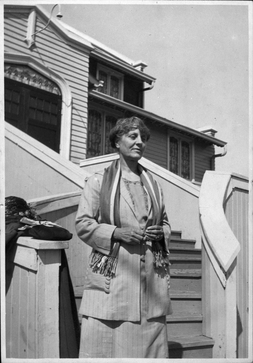A black-and-white photograph of a woman standing outside a house at the bottom of a staircase.
