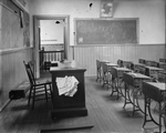 Black and white photograph of classroom with teacher's desk and rows of wooden student desks with ornamental metal legs.