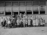 Black and white photograph of adults and young children posing in front of clapboard schoolhouse.