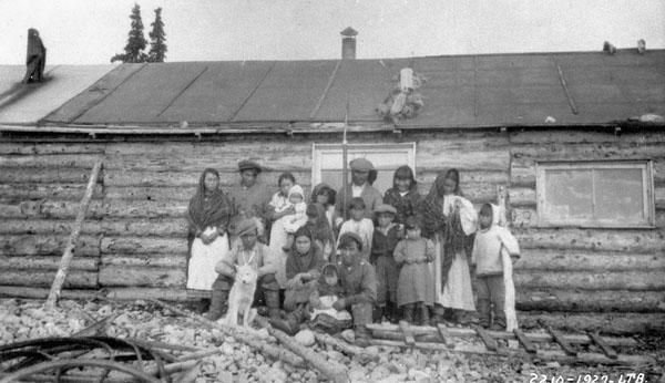 Photo de la famille Weetaltuk. Adla (extrême gauche), mariée à William, fils aîné de George (2e à partir de la gauche), George (centre) et sa première femme, Ugugak (4e à partir de la gauche). Rangée à l'avant : Alaku (extrême gauche) et Tommy (assis par terre), tous deux fils de George. (PA-099605)