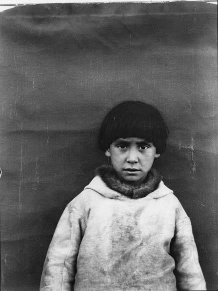 Photographie en noir et blanc d'un garçon inuit dans une parka blanche qui se tient devant une toile de fond en tissu et regarde directement l'appareil photo, Pond Inlet (Mittimatalik/Tununiq), Nunavut, août 1931