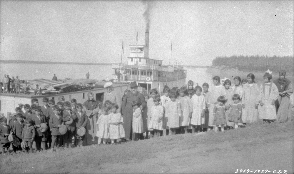 Fort Providence Indian Residential School, students and school personnel posing in front of a boat and another structure, 1927