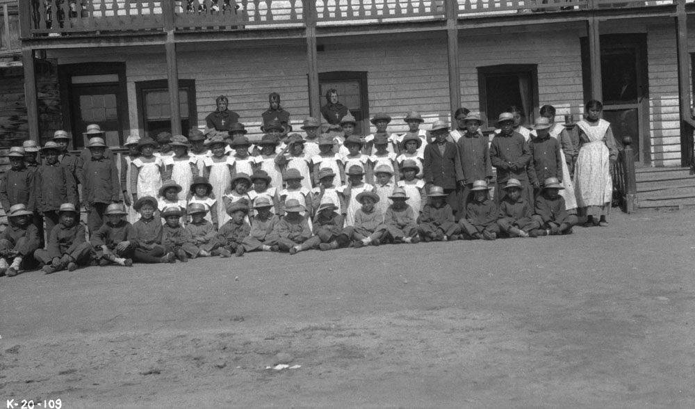 Fort Providence Indian Residential School, group of seated and standing students and nuns posing in front of the school, ca. 1920