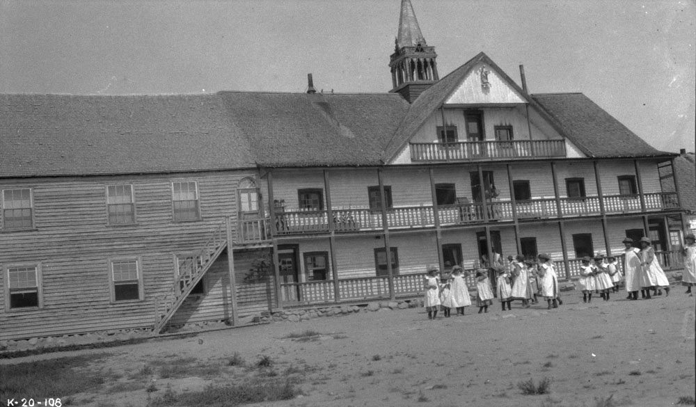 Fort Providence Indian Residential School, group of female students playing in the yard in front of the school, ca. 1920