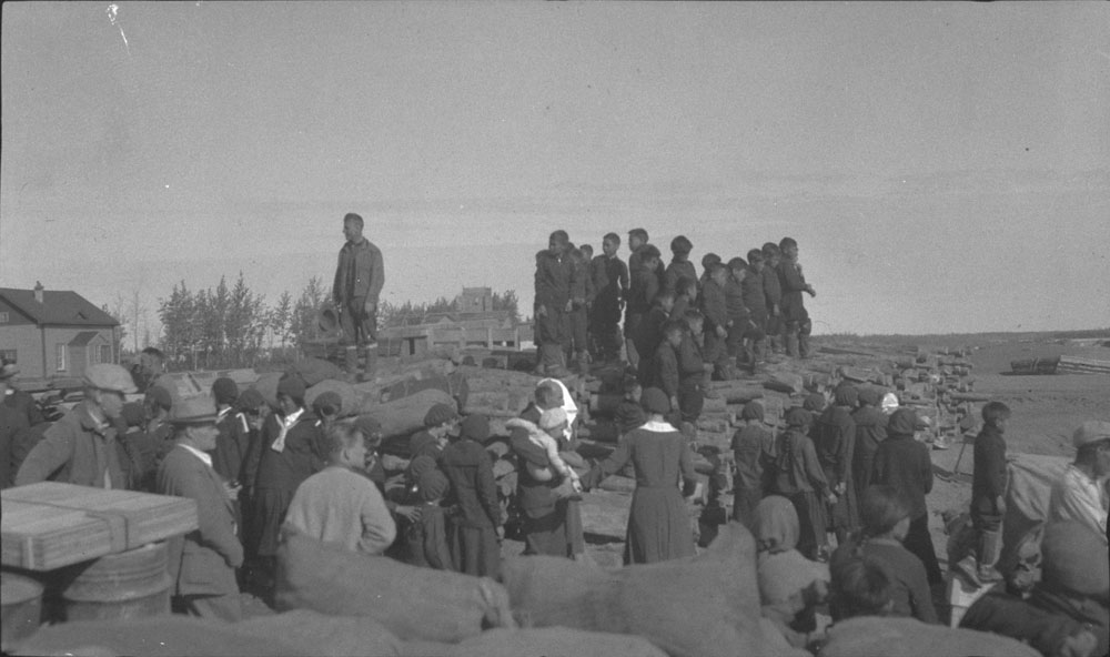 Aklavik Anglican Indian Residential School (All Saints Indian Residential School), group of students waiting at the shore for the delivery of supplies, 1937