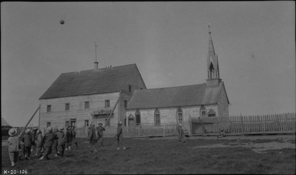 Fort Providence Indian Residential School (Providence Mission), group of boys playing with a ball in yard in front of the residence and the church, ca. 1920