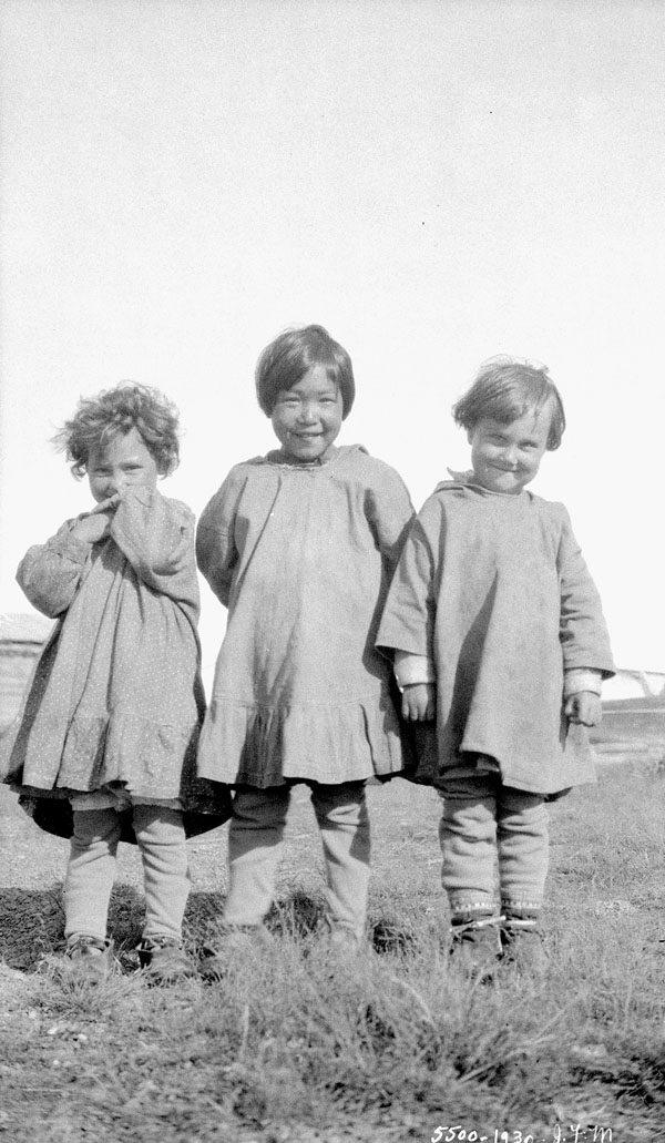 All Saints Indian Residential School, close-up view of three young girls, two Métis and one Inuit, standing on a grassy plain, Shingle Point, 1930