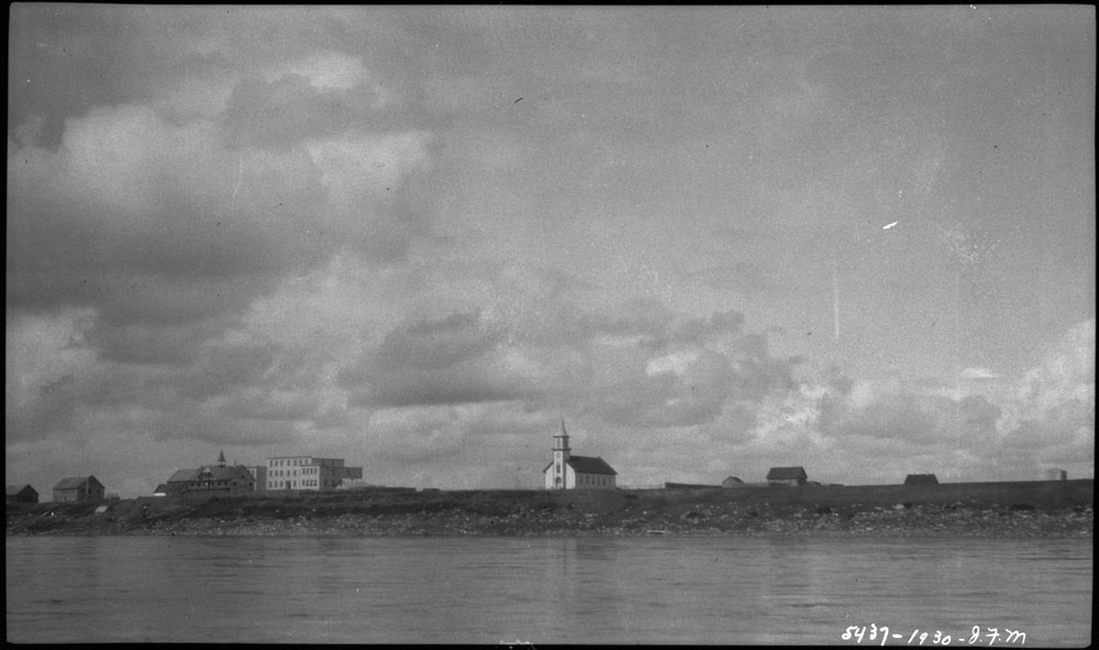 Fort Providence Indian Residential School, distant view of the school, the church and other buildings from the Mackenzie River, 1930