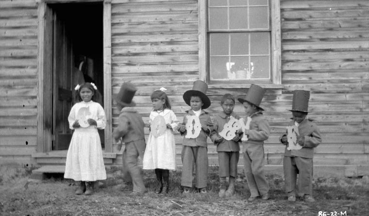 Fort Simpson Indian Residential School, seven children standing beside the school holding letters that spell Goodbye, 1922