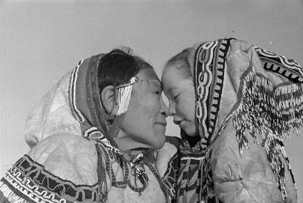 Black and white photograph of a woman and child wearing beaded parkas, facing each other with their noses gently pressed together.