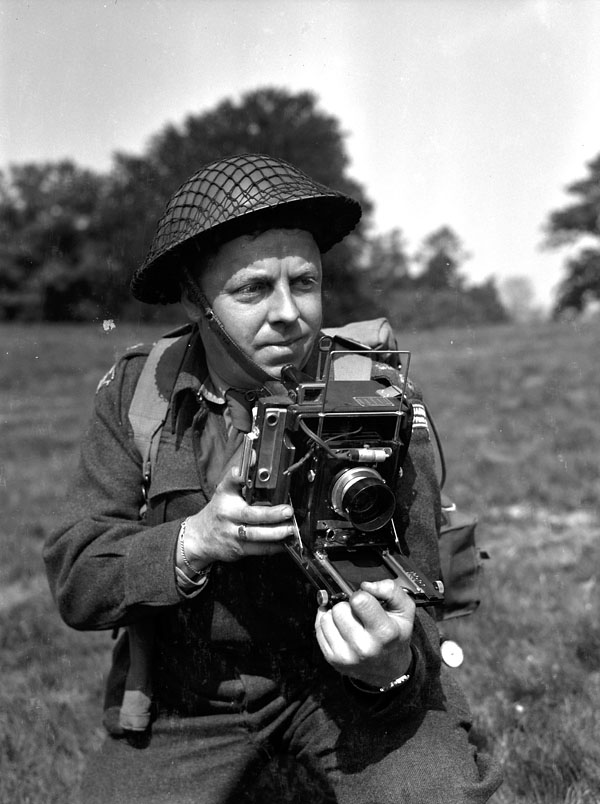 Lieutenant Frank L. Dubervill of the Canadian Army Film and Photo Unit, holding an Anniversary Speed Graphic camera