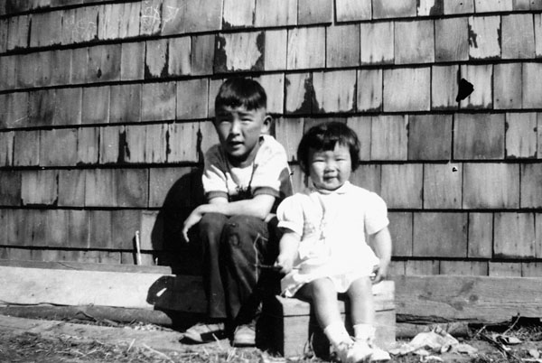 Young boy and girl sitting next to a shingled house