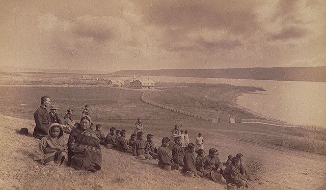 Fort Qu'Appelle Indian Residential School, students and family members sitting on a hill overlooking the school, Lebret, May 1885