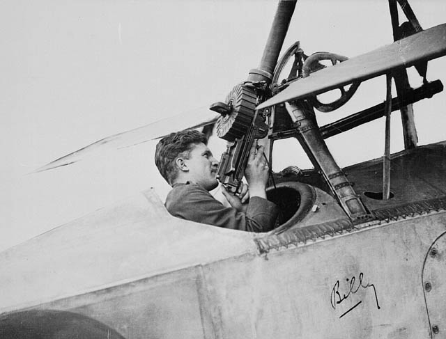 Photo of man seated in the open cockpit of an airplane and holding a machine gun.