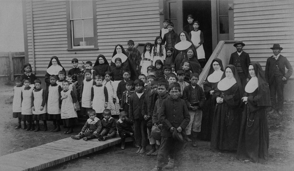 Port Harrison (Inukjuak) Federal Hostel, group of students, nuns and Aboriginal men posing in front of the school, Quebec, ca. 1890