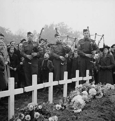 Photo of 3 men playing the bagpipes in front of a crowd of people with crosses marking graves in foreground