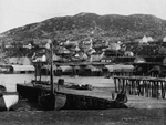 Black and white photograph of boats in a harbour and a village on a hill in the distance