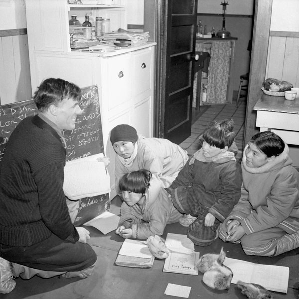 Baker Lake (Qamanittuaq) Federal Hostel, Anglican missionary Reverend W. James with four children seated on the floor during catechism class, March 1946