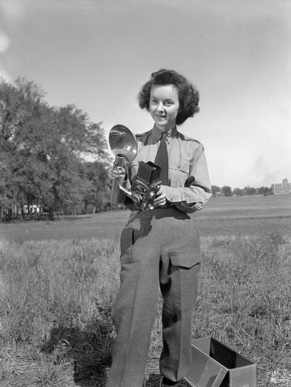 Sergeant Karen M. Hermiston of the Canadian Women's Army Corps, holding a Rolleiflex camera