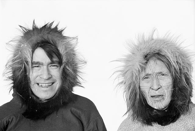 Photographie en noir et blanc d'un homme et d'une femme inuits qui portent des parkas avec capuchons bordés de fourrure, Kugluktuk, Nunavut, vers 1949-1950