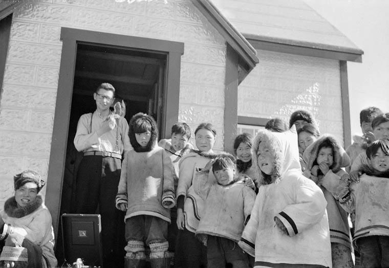 Roman Catholic Mission, Father Trinell standing in the doorway to the church with group of children in the foreground, Cape Dorset (Kinngait), October 1951