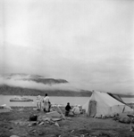 Black and white photograph of people beside a canvas tent looking at a ship