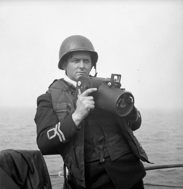 Lieutenant Gilbert A. Milne of the Royal Canadian Naval Volunteer Reserve, holding a Fairchild K20 camera
