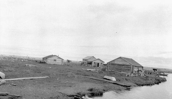 Pensionnat indien de Shingle Point (mission anglicane de St. John's), vue lointaine du pensionnat pour filles (à gauche), de l'ancien magasin de la Compagnie de la Baie d'Hudson (au centre) et du vieil entrepôt (à droite), 1930