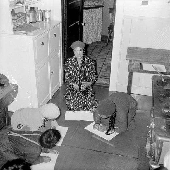 Baker Lake (Qamanittuaq) Federal Hostel, students of Reverend W. James kneeling on the floor doing schoolwork, 1948