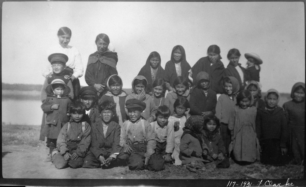 Hay River Indian Residential School (St. Peter's Mission), group of students of varying ages posing outdoors on their way to the school, 1931