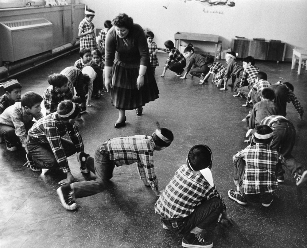 Bishop Horden Hall (Moose Factory Indian Residential School), Cree students wearing headbands with feathers and moving in a circle in classroom, Moose Factory Island, ca. 1950