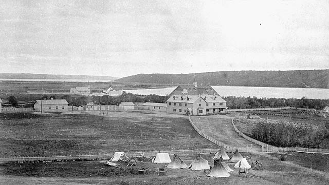 Fort Qu'Appelle Indian Residential School, distant view with tents, carts and teepees at the fence perimetre, Lebret, [May 1885?]