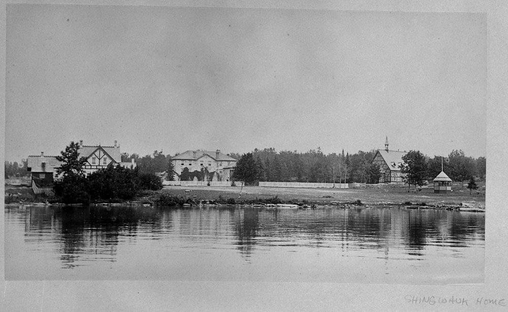 Shingwauk Indian Residential School, distant view from St. Mary's River of the school, chapel and another building, Sault Ste. Marie, ca. 1900