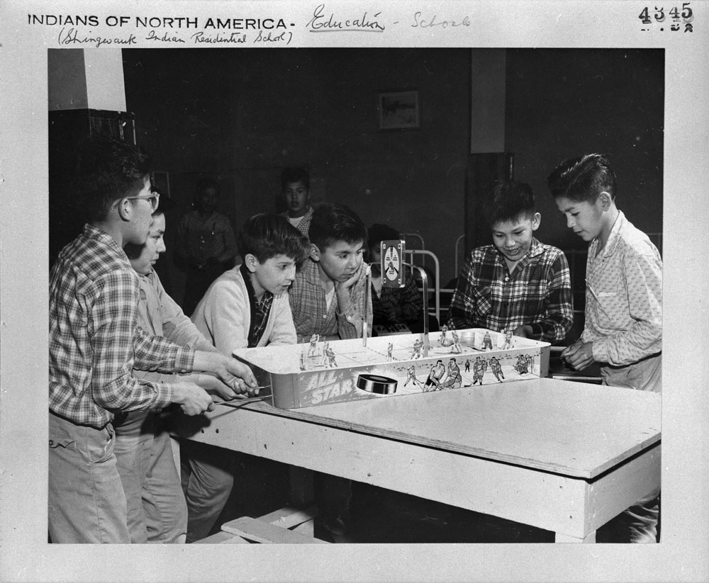 Shingwauk Indian Residential School, junior boys (left to right) Charlie Matoush, Allan Saganash, Jerry Wynn, Willy Ottereyes, Francis Pine, and Tommy Friday playing table hockey in their dormitory, Sault Ste. Marie, ca. 1960