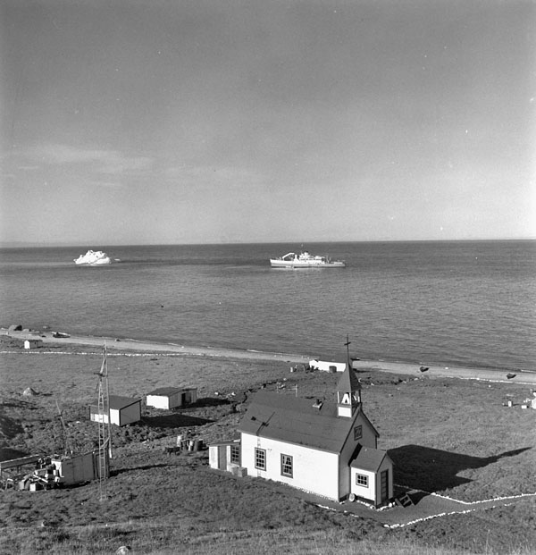 Roman Catholic Mission, aerial view of the church with the CGS C.D. Howe anchored offshore in the background, Pond Inlet, (Mittimatalik/Tununiq), Nunavut,  July 1951