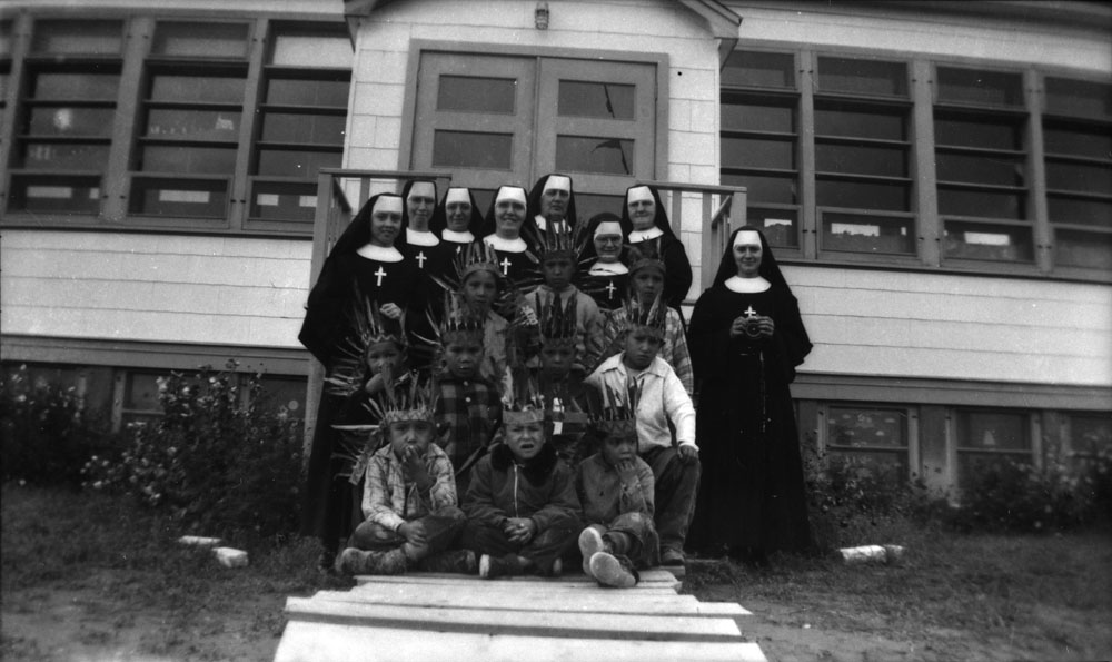 Pukatawagan Indian Residential School, students with nuns from the Soeurs du Sacré-Coeur d'Ottawa in front of the school, ca. 1960