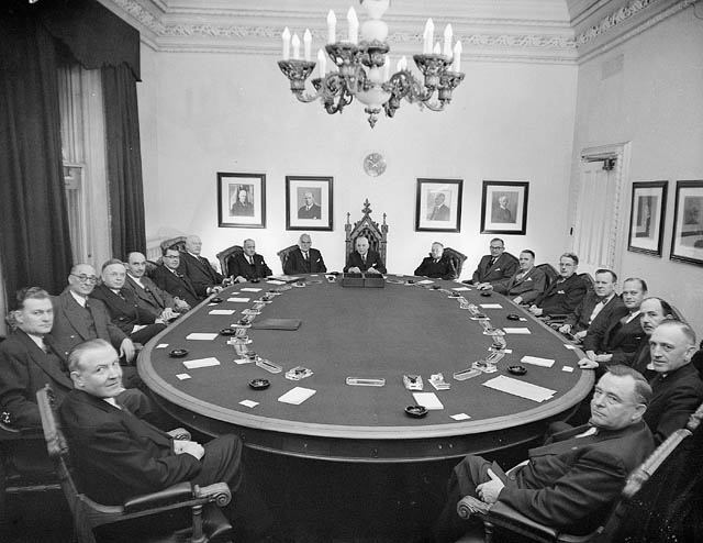 Photograph taken in April 1953 of 19 Cabinet members sitting around an oblong table.