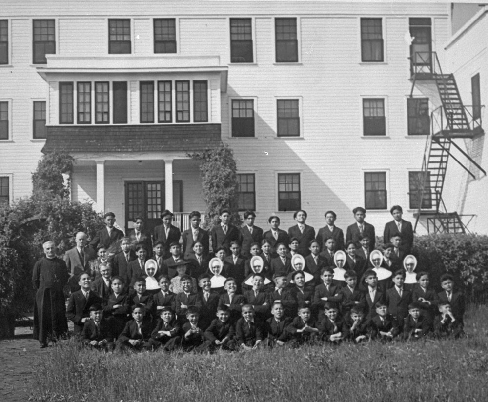 St. Anthony's Indian Residential School, male students with nuns, a priest, and school personnel, Onion Lake, ca. 1950